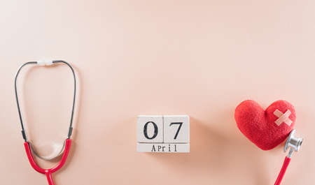 Top view of doctor stethoscope with wooden calendar and red heart on pastel background. World health day and medical concept.