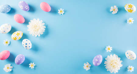 Happy easter! Colourful of Easter eggs in with flower on pastel blue background. Greetings and presents for Easter Day celebrate time. Flat lay ,top view. Zdjęcie Seryjne