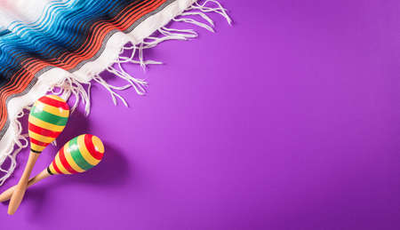 Cinco de Mayo holiday background made from maracas, mexican blanket stripes or poncho serape on purple background.