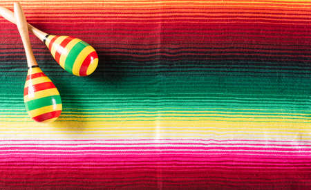 Cinco de Mayo holiday background made from maracas on mexican blanket stripes or poncho serape background.