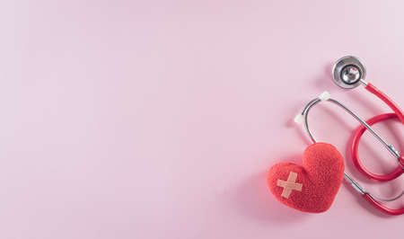 Top view of doctor stethoscope and red heart on pastel background. World health day and medical concept.