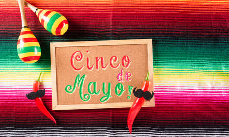 Cinco de Mayo holiday background made from maracas and chili on  mexican blanket stripes or poncho serape background with the text.