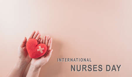 Hand holding red heart on pastel background. International nurse day and medical concept.