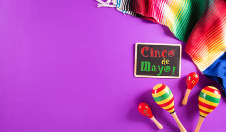 Cinco de Mayo holiday background made from maracas, mexican blanket stripes or poncho serape on purple background with the text.