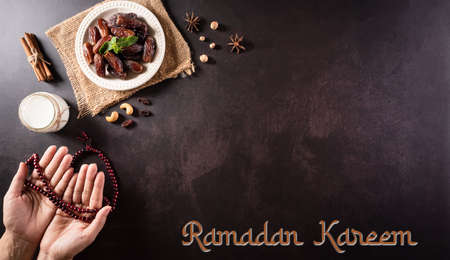 Ramadan Kareem background concept, Hands holding rosary bead with dates fruit and milk on dark stone background. Zdjęcie Seryjne
