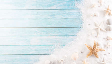 Summer holiday, travel and vacation concept. Beach sand with starfish and seashell on pastel blue wooden background. Zdjęcie Seryjne