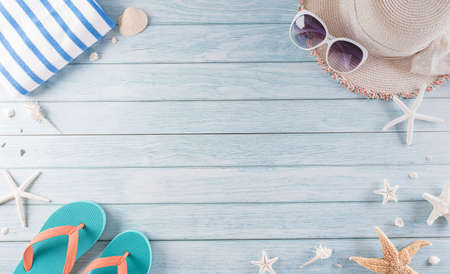 Summer holiday, travel and vacation concept. Sunglasses, starfish, beach hat, flip flop and sea shell on pastel blue wooden background.