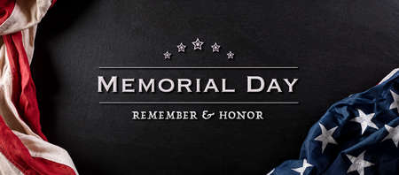 Happy memorial day concept made from vintage american flag with text on black wooden background.