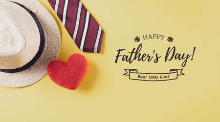 Happy Father's Day inscription with colorful tie, red heart and hat on pastel yellow background. Zdjęcie Seryjne