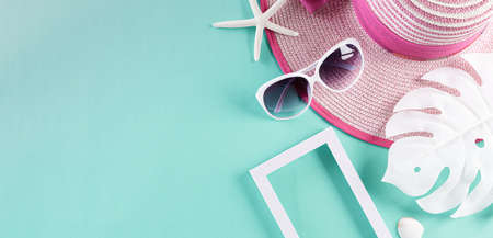 Beach accessories including sunglasses, starfish, beach hat and seashell on green pastel background for summer holiday and vacation concept.