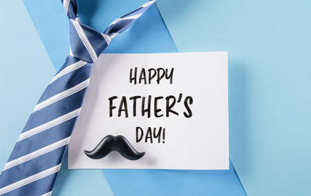 Happy Father's Day inscription in celebrated card and plaid tie on pastel blue background