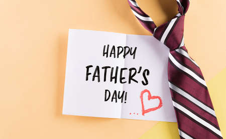 Happy Father's Day inscription in celebrated card and plaid tie on pastel background