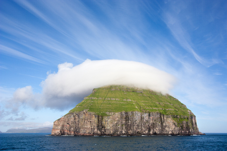 lenticular cloud: Litla Dimun, the smallest of Faroe Islands, caught from the sea with a curious hat of clouds in a clean sky . One of the most striking feature of this island is that it often remains covered in clouds. This type of cloud is known as Lenticular clouds, so