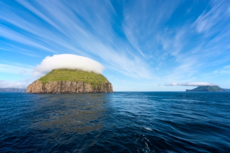 lenticular: Litla Dimun, Faroe Islands. Small green island covered by lenticular clouds. Stock Photo