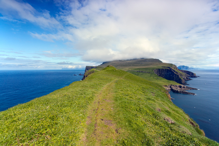 Faroe Islands, Mykines . Path in unspoilt nature with sea on both sides