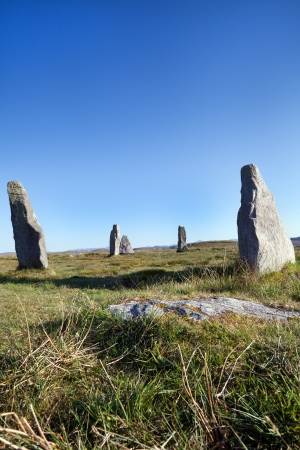 alignments: The ancient standing stones of Callanish (or Calanais) on Lewis in the Outer Hebrides of Scotland against a blue sky. Built about 5000 years ago, the stones of Callanish are arranged in alignments of avenues and a central circle not unlike a celtic cross  Stock Photo