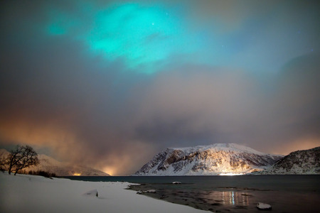 Aurora chasing during a cloudy winter night Stock Photo
