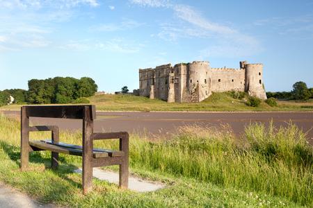 pembrokeshire: Empty bench facing Carew Castle, Pembrokeshire, Wales Stock Photo