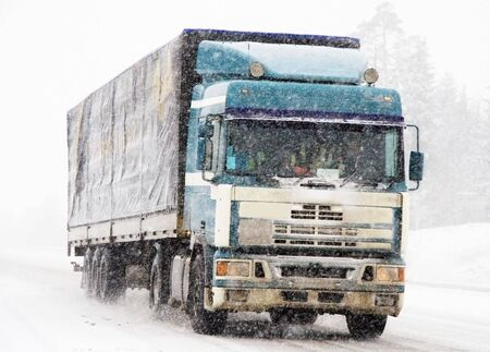 moving truck: a moving truck during a heavy snow