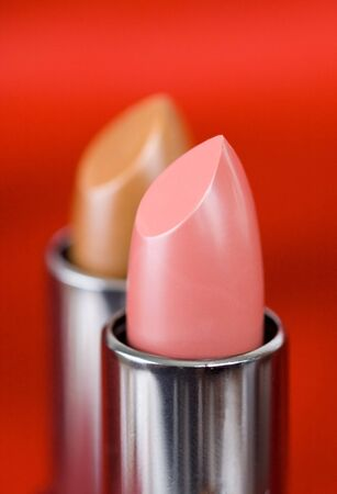 Decorative female cosmetics on a red background photo