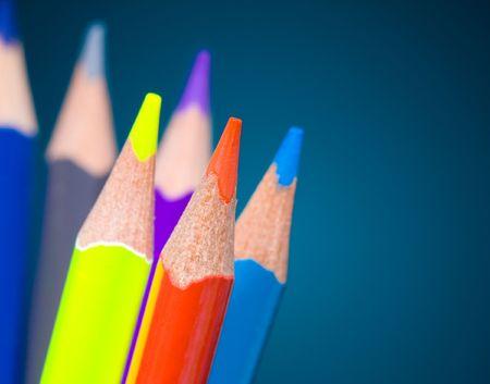Colour pencils on blue background photo