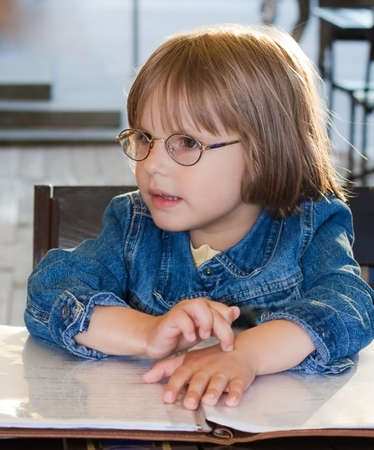 little girl sitting in cafe holding menu photo