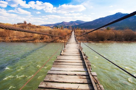 Suspended wooden bridge over a river photo