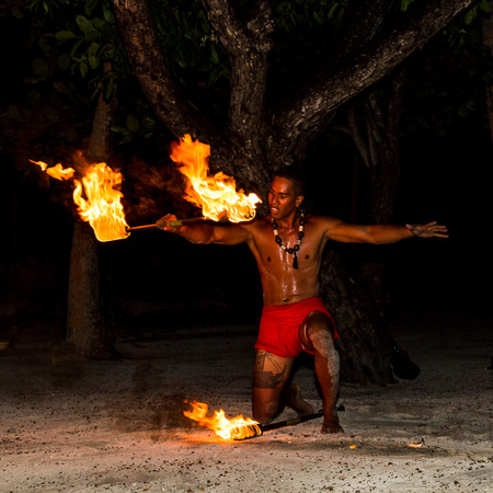 TAHAA, FRENCH POLYNESIA - CIRCA 2014: Polynesian man perform traditional fire dance circa 2014 in Tahaa.Fire dance is popular tourist attraction on luxury resorts of French Polynesia.