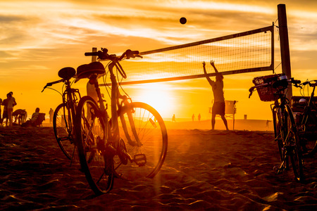 유명한 로스 앤젤레스 랜드 마크에서 석양 ligth의 자전거 및 배구 게임