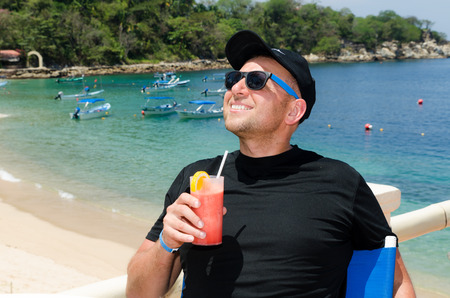 powerfull: Young caucausian man drinks coctail at ocean beach resort during  summer vacations