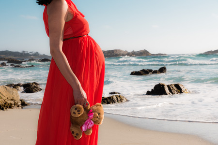 Outdoor shot of young pregnant woman in red dress