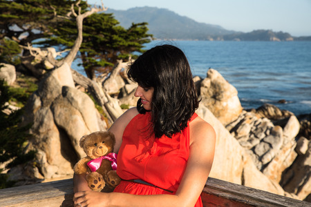 outdoor shot: Outdoor shot of young pregnant woman in red dress