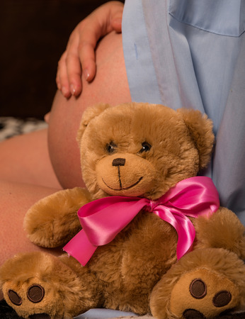 Plush toy with pink bow is sitting next to pregnant woman in lose shirt