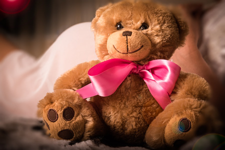 Teddy bear plush toy with pink bow is sitting next to pregnant woman