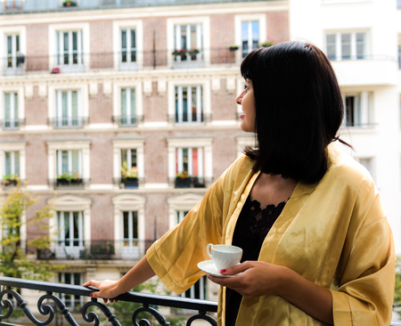 one female: Beautiful woman holding cup of coffee standing on the balcony overlooking Paris streets