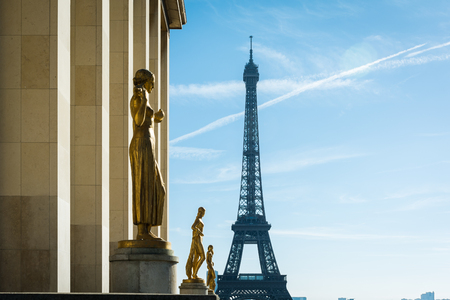 sombre: Golden colored Paris statues overlooking famous Eiffel tower Stock Photo