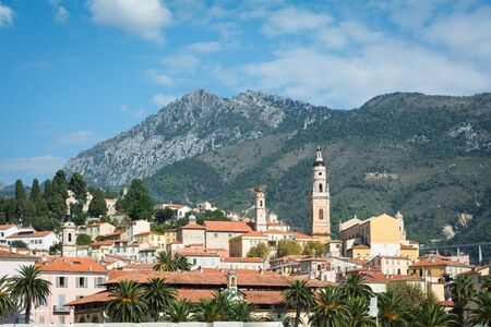 french riviera: French Riviera town Menton panorama with mountains on background Stock Photo