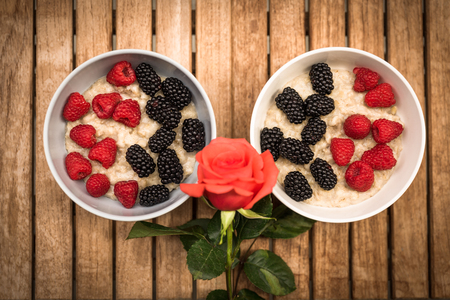 in: Couple of oatmeal bowls with berries and flower.
