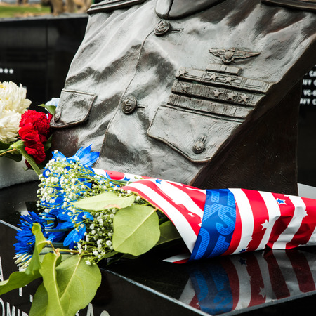 Flowers wrapped in us flag themed colors by the military monument on Memorial Day Stock Photo