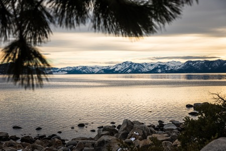 lake tahoe: Heavy sky hanging over golden light lit magnificient Lake Tahoe Stock Photo