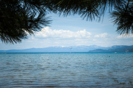 sierra nevada: Kayaks and parachutte on Lake Tahoe seen through tree branches on the shore