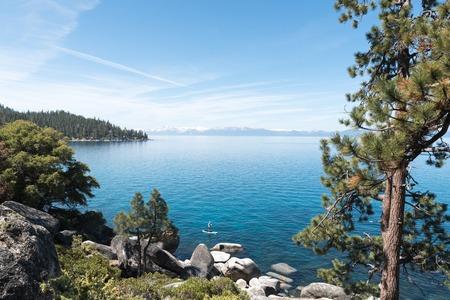 sierra nevada: Person standing on SUP rowing along Lake tahoe shorelile