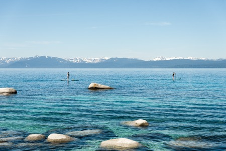 sup: People standing on SUP rowing along Lake tahoe shorelile
