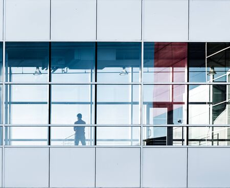 Silhouette of  standing person in the window of modern office Imagens