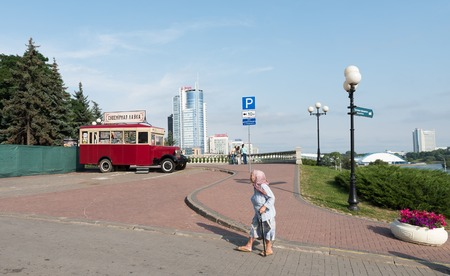 Eldery church goer passing by souvenir shop on Svobody Square