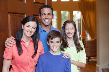 latin family: Hispanic father, caucasian mother and mixed ethinicity son and daughter standing