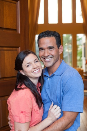 Caucasian wife and hispanic husband standing in entryway of home with tall wooden door photo