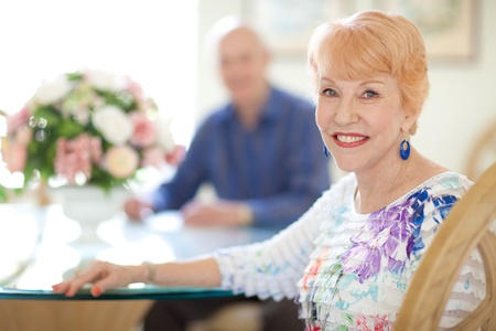 linda: Happy caucasian Senior Couple in Dining room. Female sitting looking at camera. Senior husband out of focus looking at camera. Bright and Airy.