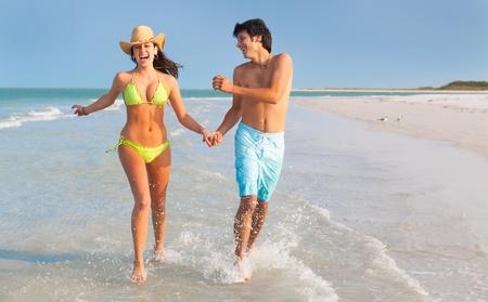 affectionate action: plano general del hombre y de la mujer latina joven corre a trav�s de las costas de Florida