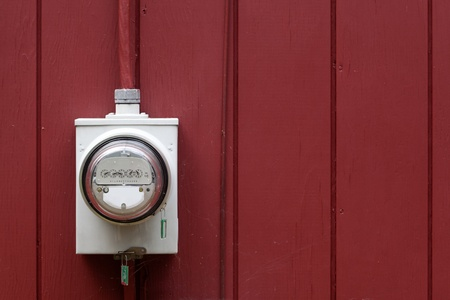 Grey electric energy meter on red painted home exterior wall. photo